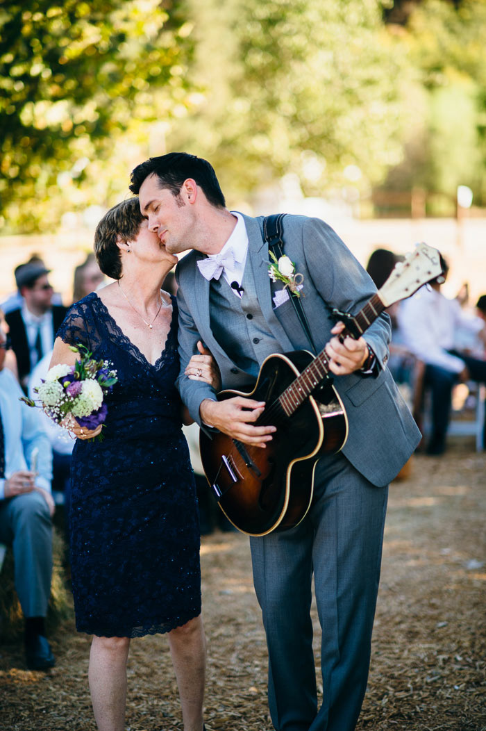 groom singing and playing guitar down aisle